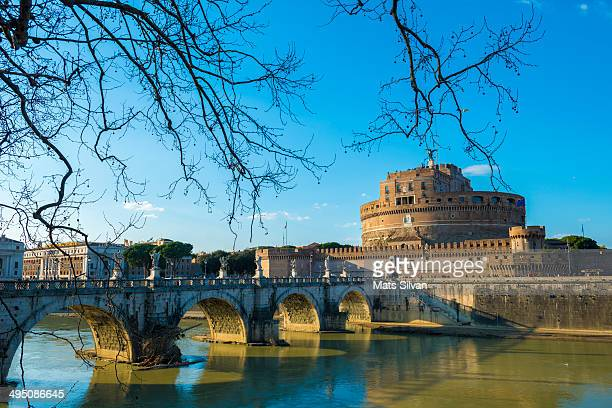 CONTENT] Castle and bridge Sant'Angelo with tree branches and blue sky over Tiber river in Rome Italy