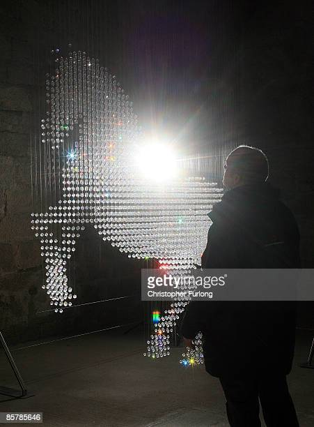 Castle custodian Michael McGreal views 'Lucky Spot' a crystal sculpture by designer and artist Stella McCartney which hangs inside the Great Hall of...