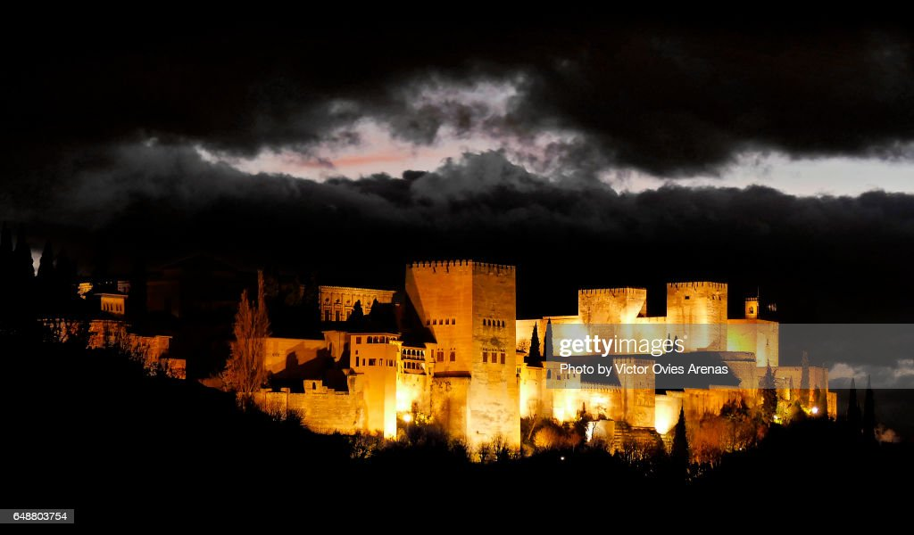 A Castle in the Clouds: The Alhambra illuminated at twilight on a dark stormy day looks like a fairy-tale castle foating in the air in Granada, Andalusia, Spain : Foto de stock