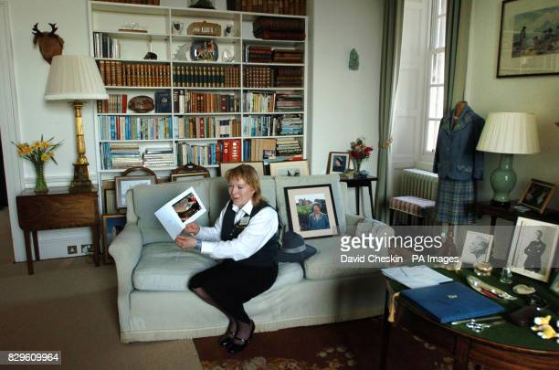 Castle of Mey staff Nancy McCarthy looks at a collection of Christmas cards sent and personally signed by the Queen Mother at the Scottish castle she...