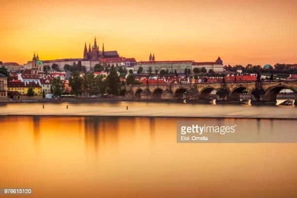 Castillo de Praga y puente de Carlos reflejan sobre el río Moldava al atardecer