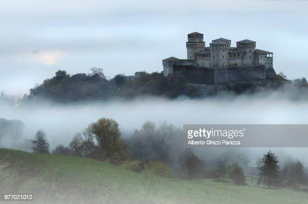 castle on hill in fog, torrechiara, parma, italy - castle stock pictures, royalty-free photos & images