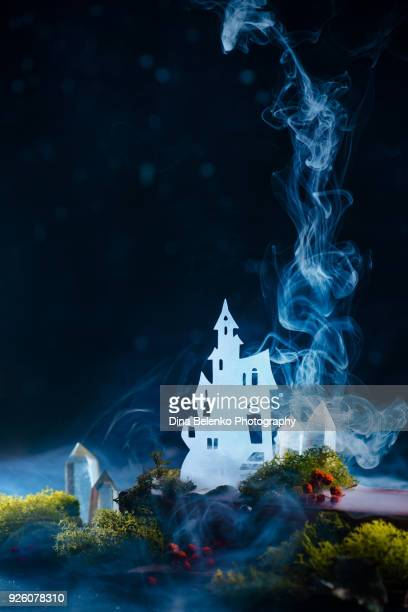 Castle silhouette shining in clouds of mystic smoke. Magic still life with moss and crystal. Modern fairytale concept with copy space.