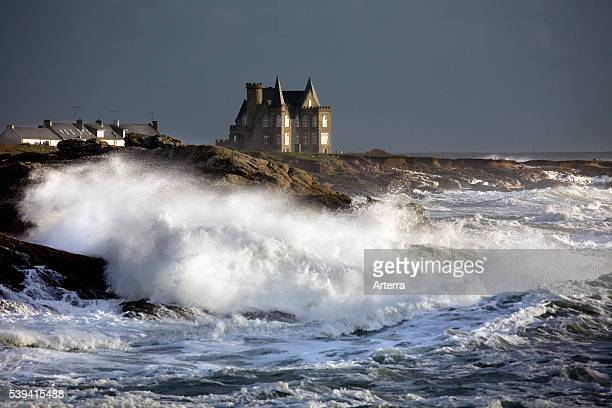 Castle Turpault and waves crashing on rocky shore during storm at sea in winter Cote Sauvage Quiberon Brittany France