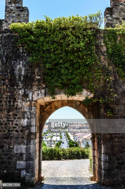 A castle wall and gate frame the view into the town of Vila Vicosa, Portugal