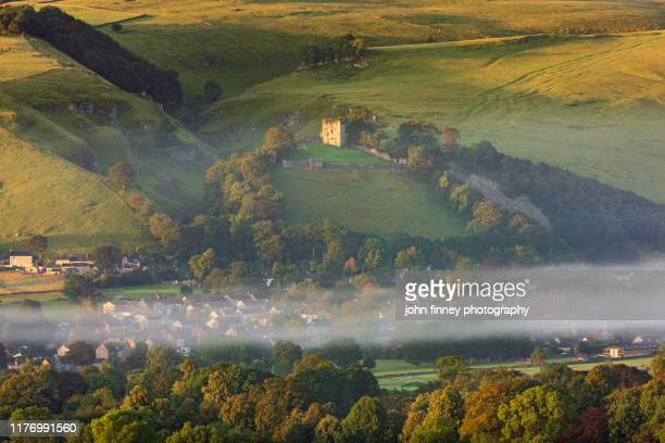 castleton's castle fort surrounded by early autumn trees with mist. peak district national park, derbyshire - peveril castle stock pictures, royalty-free photos & images
