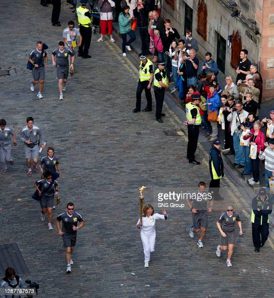 Torchbearer Lesley Forrest carries the flame up Castlehill on her way to lighting the Olympic cauldron