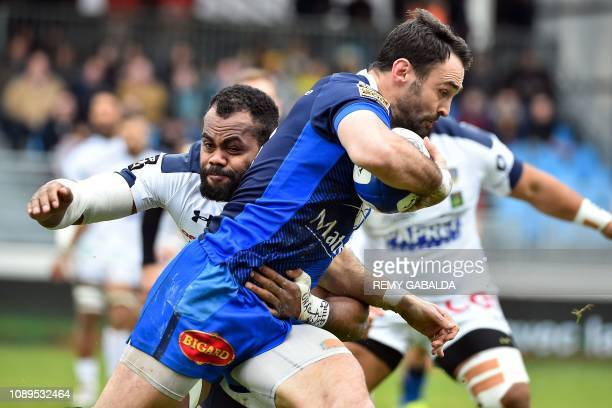 Castres' French center Thomas Combezou is tackled by Clermont's Fiji flanker Peceli Yato during the French Top 14 rugby union match between Castres...