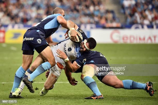 Castres' French centre Thomas Combezou is is tackled by Montpellier's South African scrumhalf Ruan Pienaar during the French Top 14 final rugby union...
