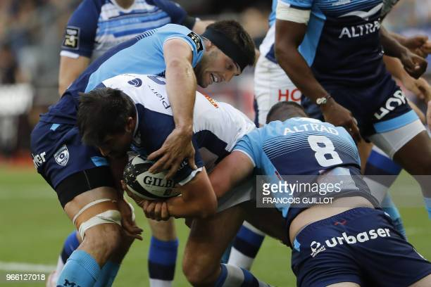 Castres' French flanker Anthony Jelonch is is tackled by Montpellier's French flanker Kelian Galletier and Montpellier's French number 8 Louis...