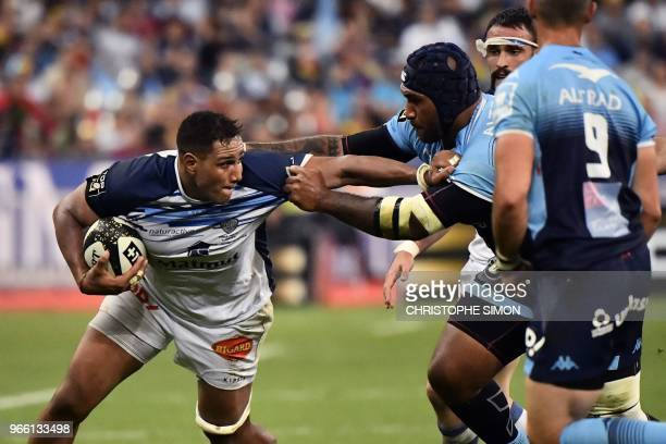 Castres' French flanker Mathieu Babillot is is tackled by Montpellier's Fijian winger Nemani Nadolo during the French Top 14 final rugby union match...