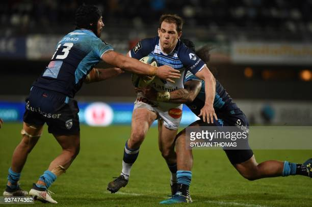 Castres French flyhalf Benjamin Urdapilleta is tackled by Montpellier's French number eight Alexandre Dumoulin and Montpellier's New Zealand number...