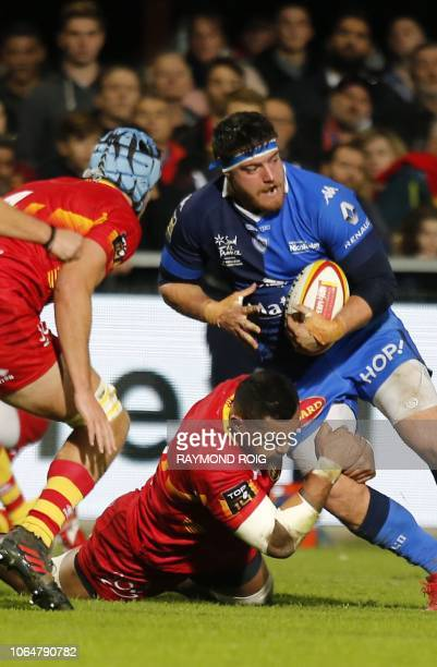 Castres French prop Antoine Tichit is tackled by Perpignan's lock Masalosalo Tutaia during the French Top 14 Rugby Union match between Perpignan and...