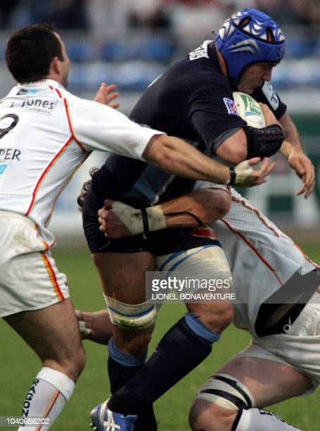 Castres n°8 Guillaume Taussac vies with Newport flanker Andrew Hall and scrumhalf Gareth Cooper during the Rugby European Cup match Castres vs...