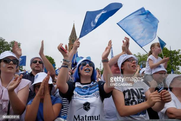 Castres supporters wave flags as they celebrate with their team after they won the French Top 14 rugby union championship in the city centre of...