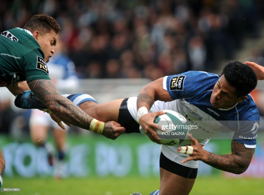 Castres's winger David Smith (R) is tackled by Pau's fijian centre Jale Vatubua during the French Top 14 rugby union match between Section Paloise and Castres Olympique at Hameau Stadium in Pau on March 12 2017. /