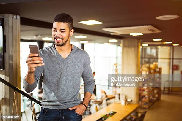 Casual African American businessman reading text message on cell phone.