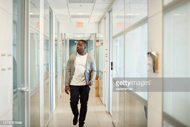 casual black freelancer in mid 20s walking in miami office - approaching stock pictures, royalty-free photos & images