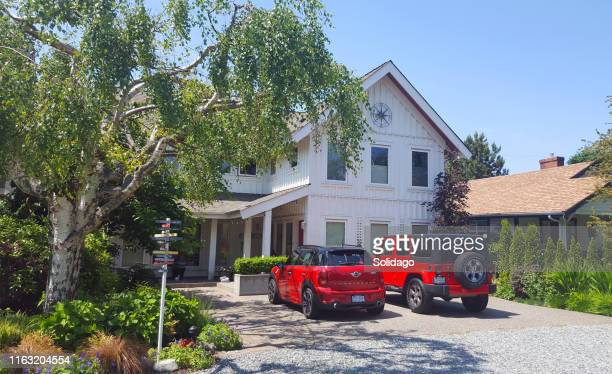 casual board and batten home with two fun red vechicles - driveway stock pictures, royalty-free photos & images