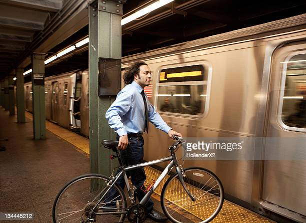 casual business man with bike on subway platform