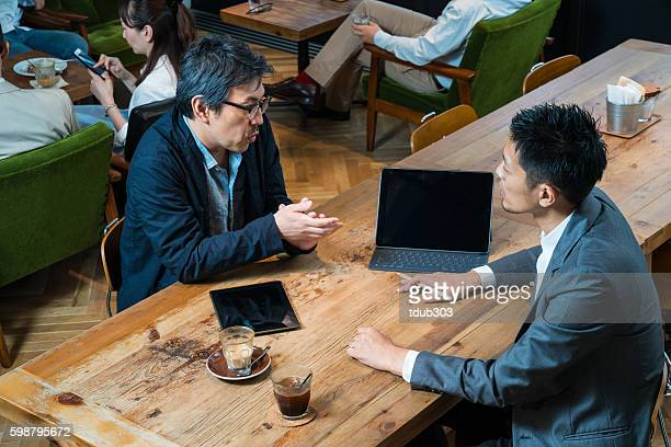 casual business meeting in cafe with a large digital tablet - nur japaner stock-fotos und bilder