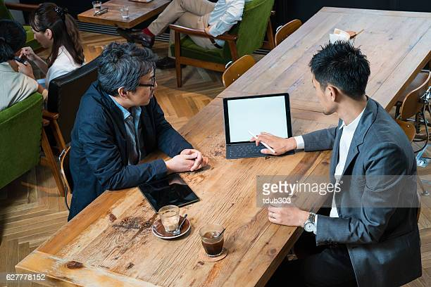 Casual business meeting in cafe with a large digital tablet