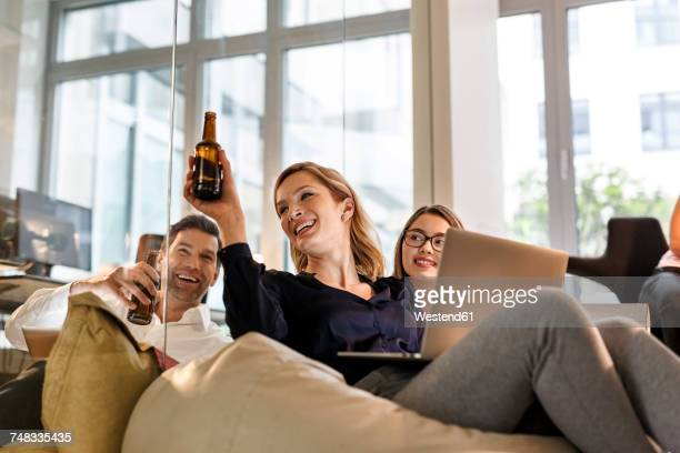 casual business people clinking beer bottles in office - after work stock photos and pictures