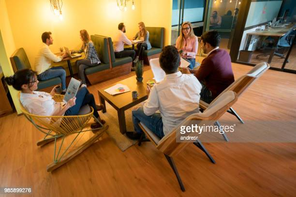 casual business people talking at a co-working office - coworking stock photos and pictures