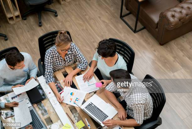 casual business people working together at a co-working space - business plan stock pictures, royalty-free photos & images