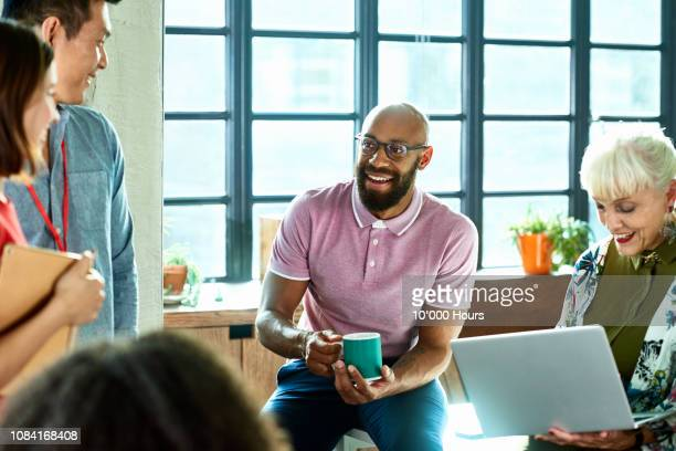 casual business team in informal morning meeting - vitality stock pictures, royalty-free photos & images