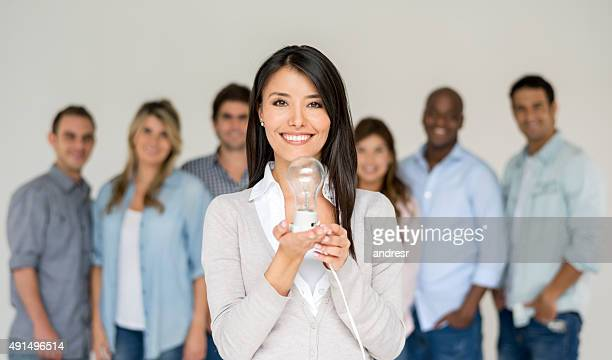 Casual business woman holding a light bulb