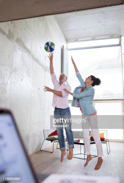 casual businessman and businesswoman playing basketball in a loft - drive ball sports stock pictures, royalty-free photos & images