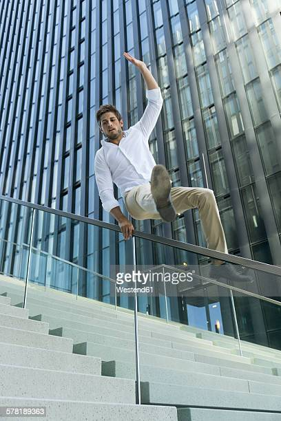 Casual businessman crossing railing at stairs