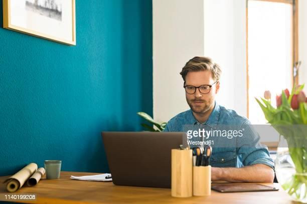 casual businessman in home office working at his laptop - hommes d'âge moyen photos et images de collection