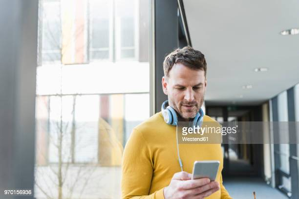 casual businessman in office using smartphone - gelb stock-fotos und bilder