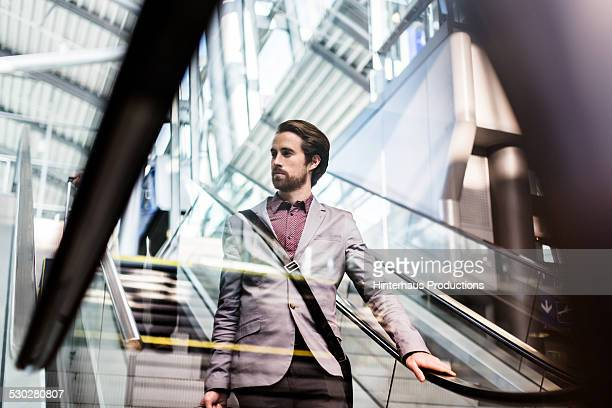casual businessman on escalator at airport - geschäftsreise stock-fotos und bilder