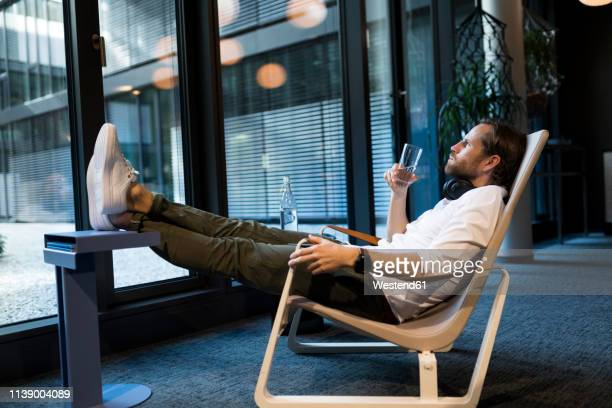 casual businessman relaxing in lounge area of a coworking space - feet up stock pictures, royalty-free photos & images