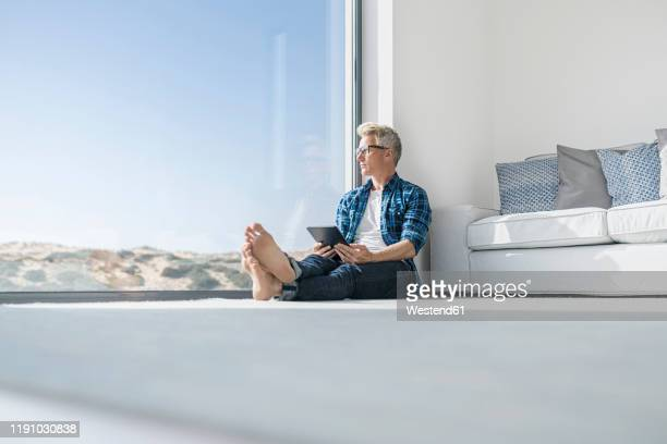 casual businessman sitting in front of window in modern home holding tablet - front view photos et images de collection