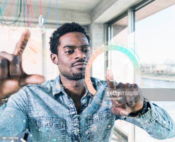 Casual businessman touching glass pane with data in office