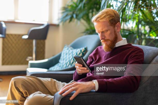 casual businessman using his phone in a lounge or bar - {{asset.href}} stock pictures, royalty-free photos & images