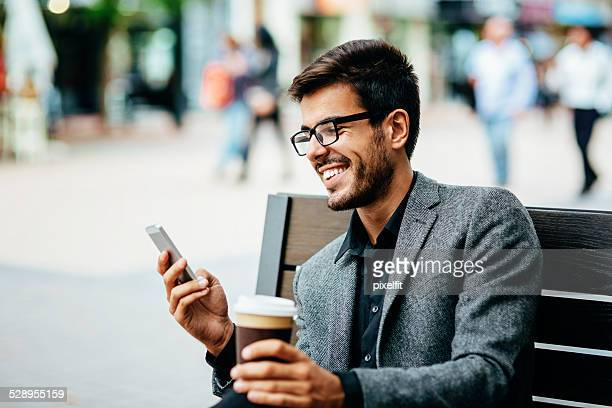 Casual businessman with phone and coffee texting outdoors