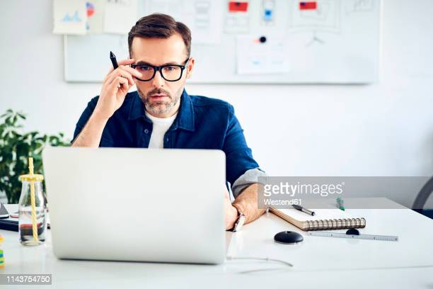 casual businessman working on laptop at desk in office - rolled up sleeves stock photos and pictures