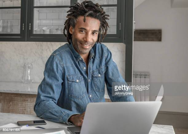 Casual businessman working on laptop at home wearing denim shirt