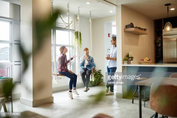 casual businesspeople talking on break in coworking office - distant stock pictures, royalty-free photos & images