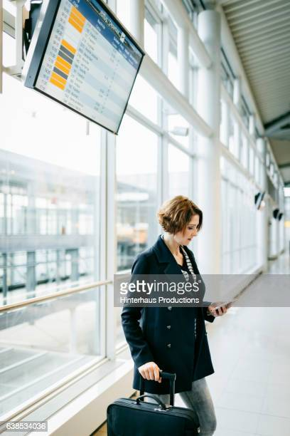 Casual businesswoman checking her smart phone at the airport
