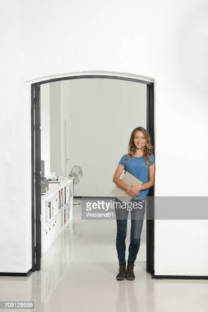 casual businesswoman in office leaning against door frame, holding folder - gründer stock-fotos und bilder