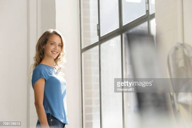 Casual businesswoman in office looking out of window