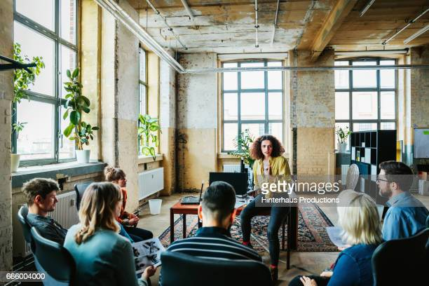 casual businesswoman leading an informal team meeting - liderança - fotografias e filmes do acervo