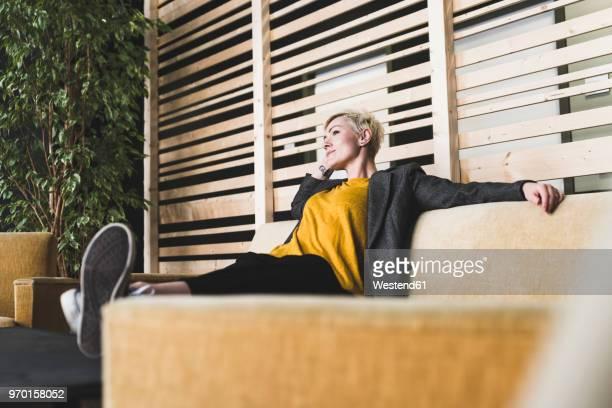 casual businesswoman sitting on couch in lounge - pause machen stock-fotos und bilder