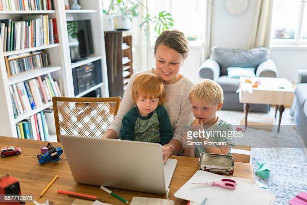 Casual businesswoman with two sons working at home
